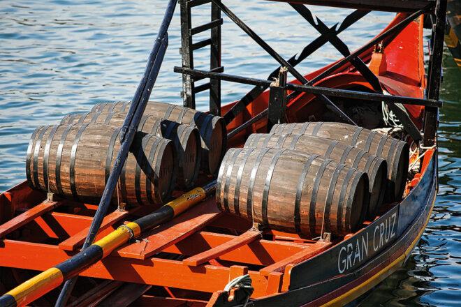 Foto eines Schiffes mit Portweinfässern an der Ribeira in Porto